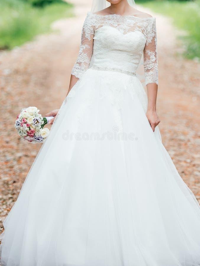 Mooie bruid in de witte kleding van het kanthuwelijk met huwelijksboeket royalty-vrije stock foto