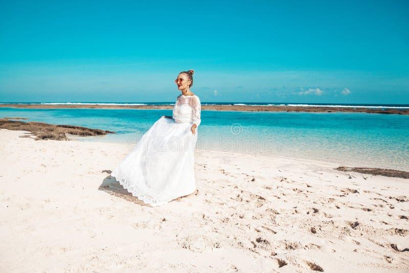 Mooie bruid die op het strand achter blauwe hemel en overzees dansen royalty-vrije stock foto