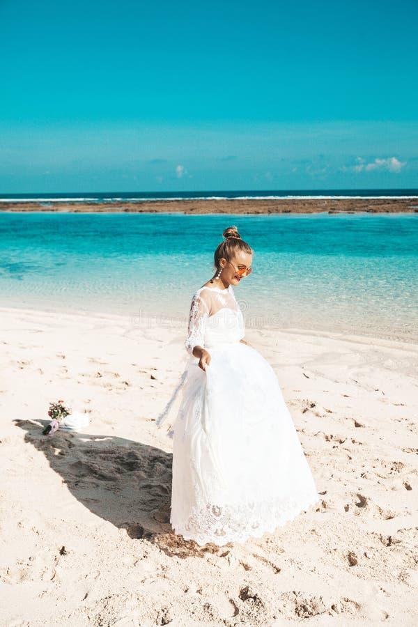 Mooie bruid die op het strand achter blauwe hemel en overzees dansen royalty-vrije stock afbeelding