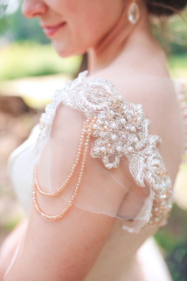 Mooie bruid die in uitstekende witte kleding in het park lopen Schitterende modieuze bruid stock afbeelding