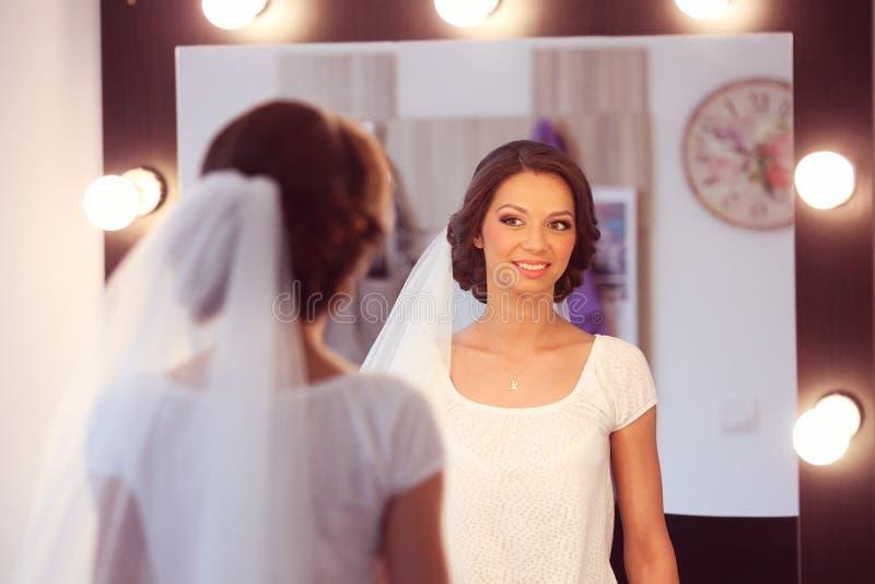 Mooie bruid die zich in de spiegel bekijken stock foto