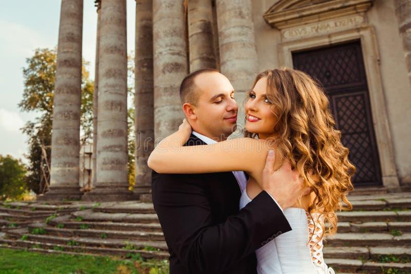 Mooie bruid die zich in groom& x27 bevinden; s omhelzingen royalty-vrije stock afbeeldingen