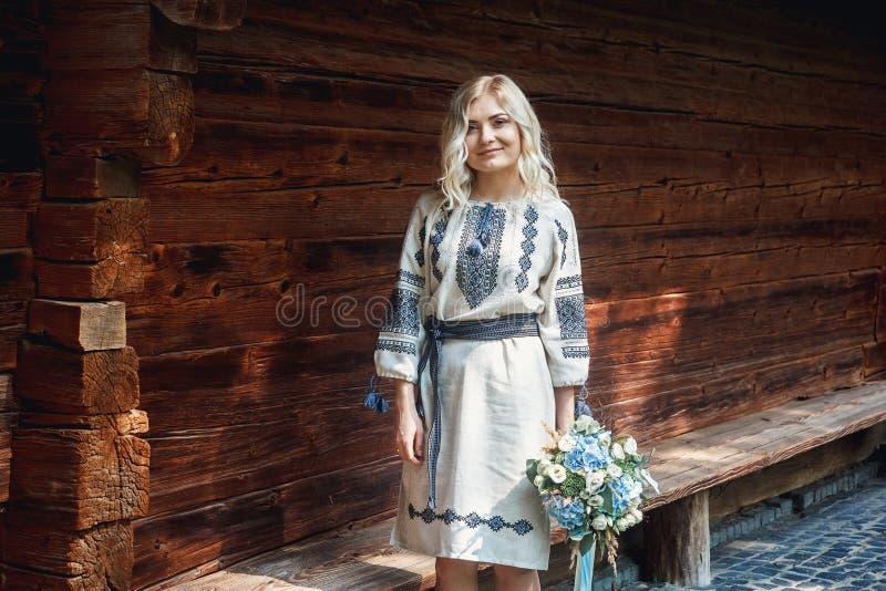 Mooie bruid in een geborduurd overhemd met een bos van bloemen op de achtergrond van een blokhuis royalty-vrije stock foto's