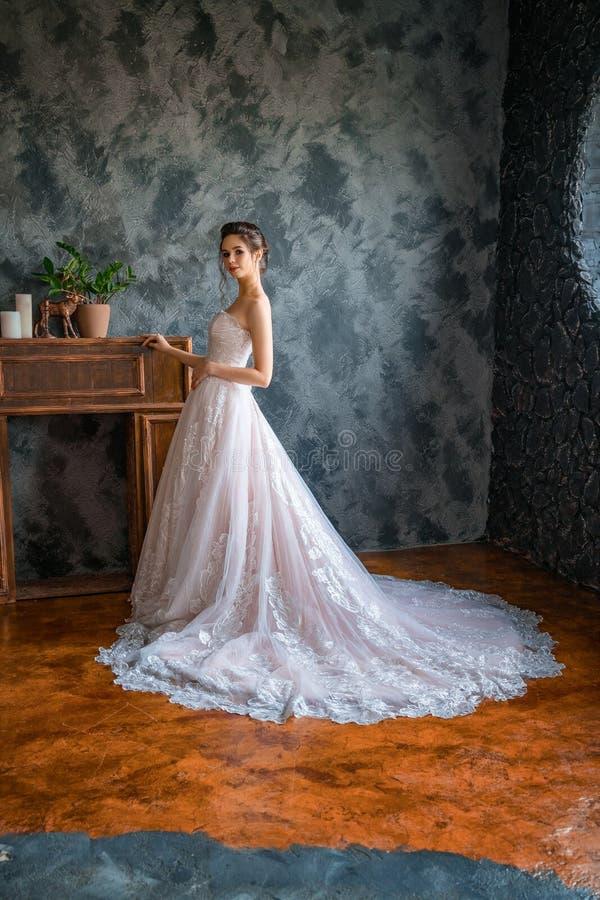 Mooie bruid in een lange kleding door het venster stock foto's