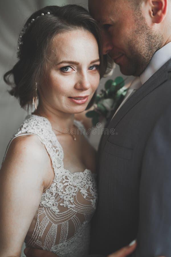 Mooie bruid en bruidegom die en op hun huwelijksdag omhelzen kussen stock afbeeldingen