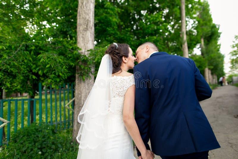 Mooie bruid en bruidegom die in openlucht het kussen op hun huwelijksdag omhelzen stock afbeeldingen