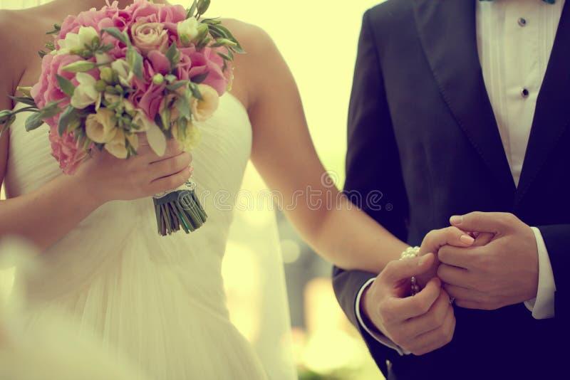 Mooie bruid en bruidegomholdingshanden royalty-vrije stock afbeelding