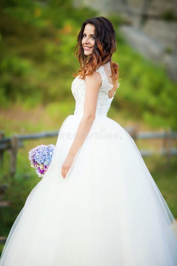 Mooie bruid in gelukkige huwelijkskleding en bruids boeket, onlangs royalty-vrije stock afbeeldingen