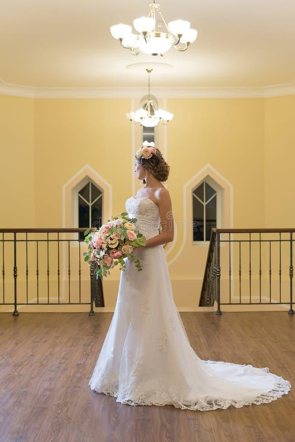 Mooie bruid in het centrum van een reusachtige mooie ruimte stock foto's