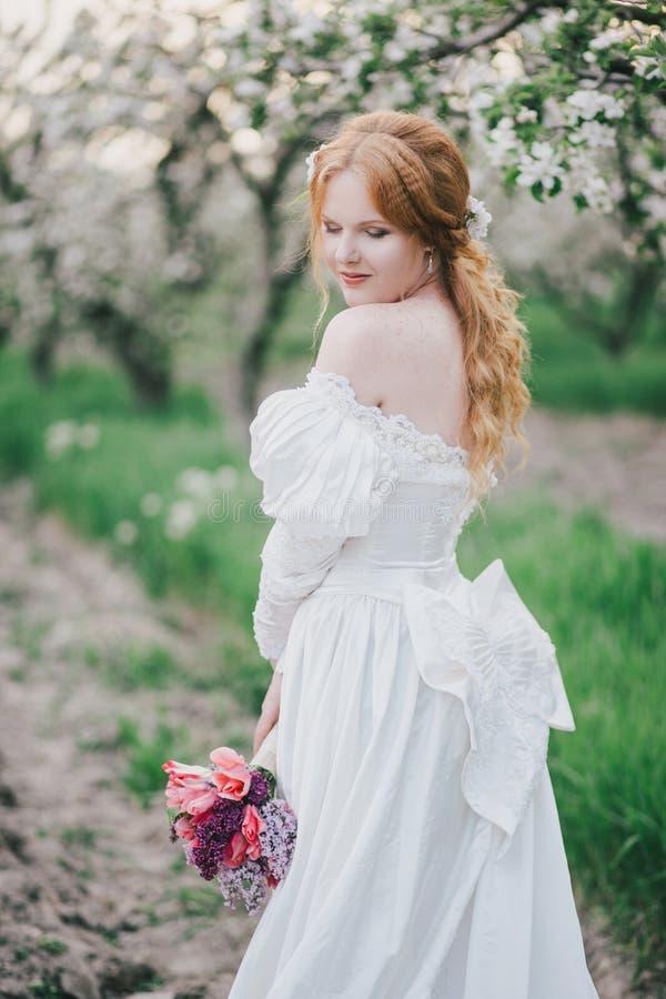 Mooie bruid in het uitstekende huwelijkskleding stellen in een bloeiende appeltuin stock foto