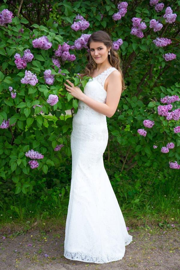 Mooie bruid in huwelijkskleding het stellen dichtbij bloeiende lilac boom royalty-vrije stock fotografie