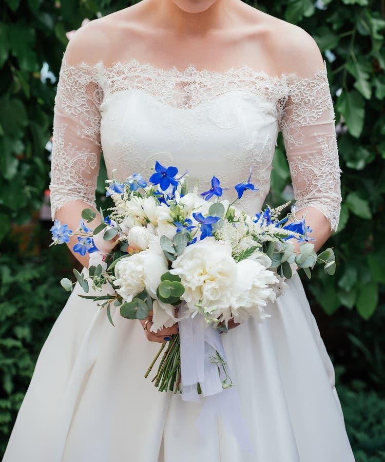 Mooie bruid in huwelijkskleding met huwelijksboeket van pioenen stock foto