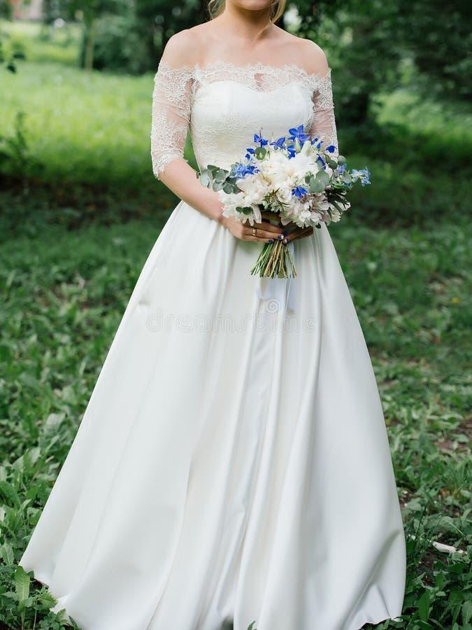 Mooie bruid in huwelijkskleding met huwelijksboeket van pioenen royalty-vrije stock foto's