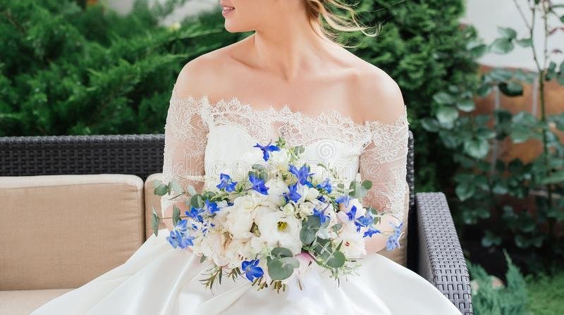 Mooie bruid in huwelijkskleding met huwelijksboeket van pioenen stock foto's