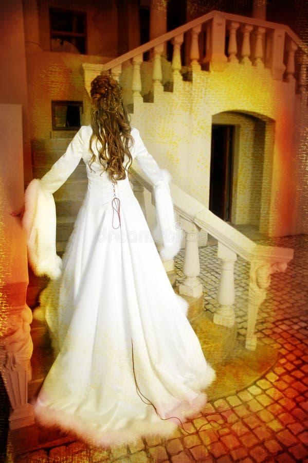Mooie bruid in lange zijdelaag op trap royalty-vrije stock foto's