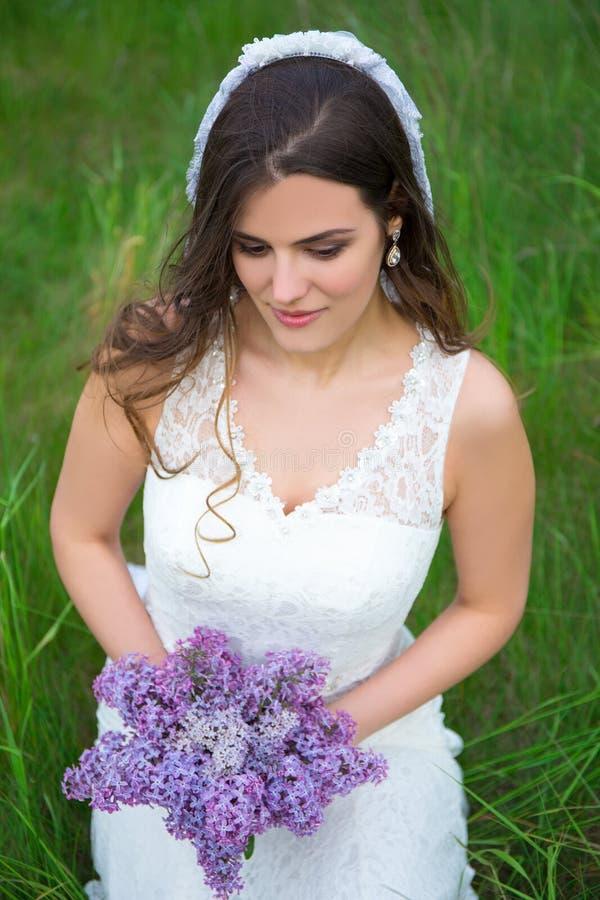 Mooie bruid met boeket van lilac bloemen stock fotografie