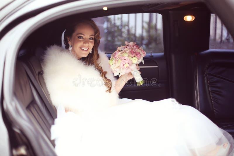 Mooie bruid met bruids boeket in auto op huwelijksdag stock afbeeldingen
