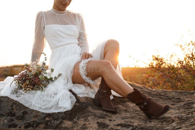 Mooie bruid met de zitting van het gebiedsboeket op rots royalty-vrije stock foto's