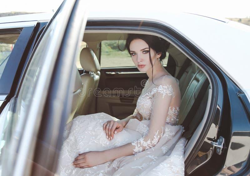 Mooie bruid met donker haar in elegante huwelijkskleding, het stellen royalty-vrije stock afbeeldingen