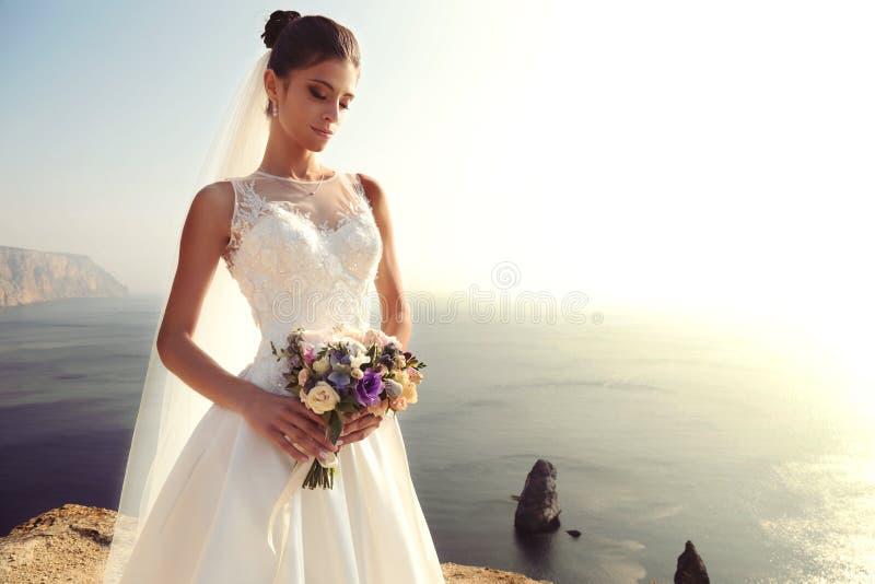 Mooie bruid met donker haar in luxueuze huwelijkskleding stock foto