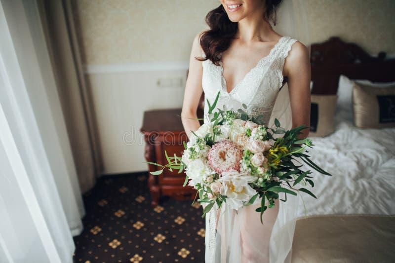 Mooie bruid met een boeket van bloemen in de hotelruimte stock fotografie