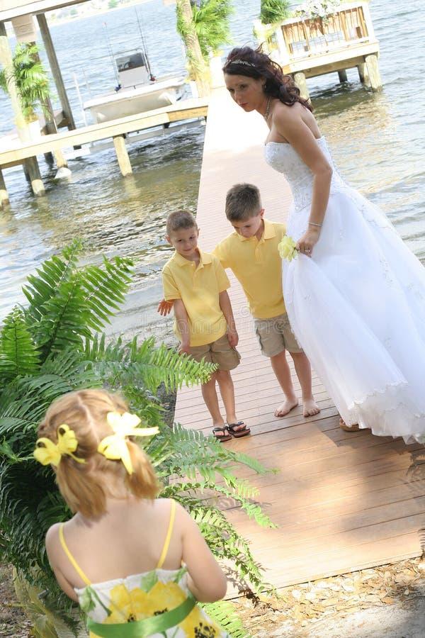 Mooie bruid met haar kinderen op dok stock foto