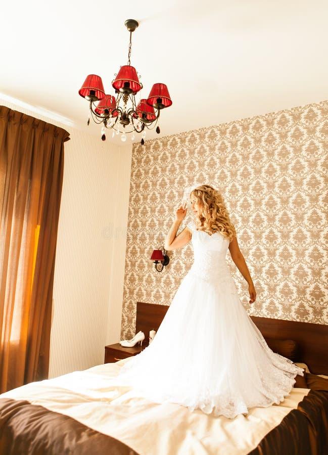 Mooie bruid met maniersluier het stellen op bed bij huwelijksochtend makeup Blondemeisje met het lange golvende haar stileren stock afbeeldingen