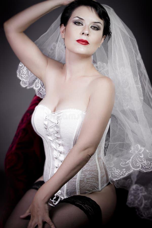 Mooie bruid met sluier en wit korset stock fotografie
