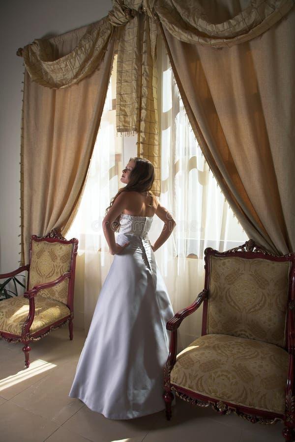 Mooie bruid naast venster stock foto's