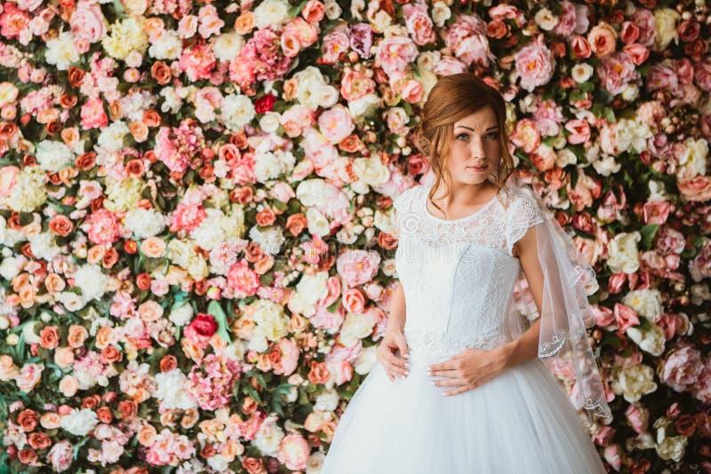 Mooie bruid op de achtergrond van een muur van bloemen stock foto's