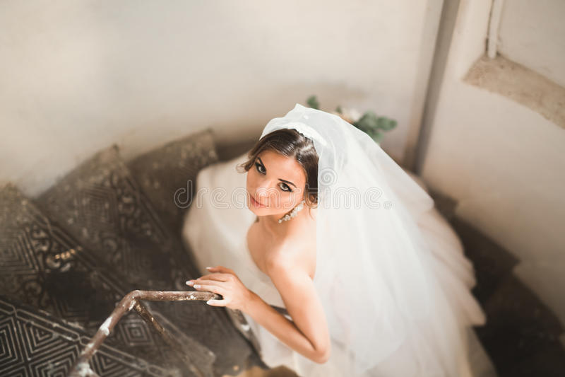 Mooie bruid in prachtige kledingstribunes alleen op treden stock afbeelding