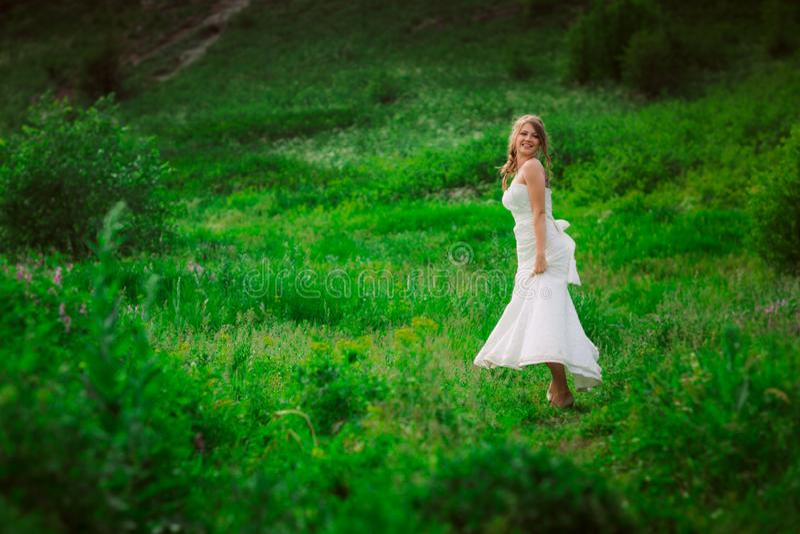 Mooie bruid tegen de achtergrond van de berg en het gras royalty-vrije stock afbeeldingen