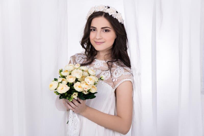 Mooie bruid in witte kleding met bloemen royalty-vrije stock fotografie