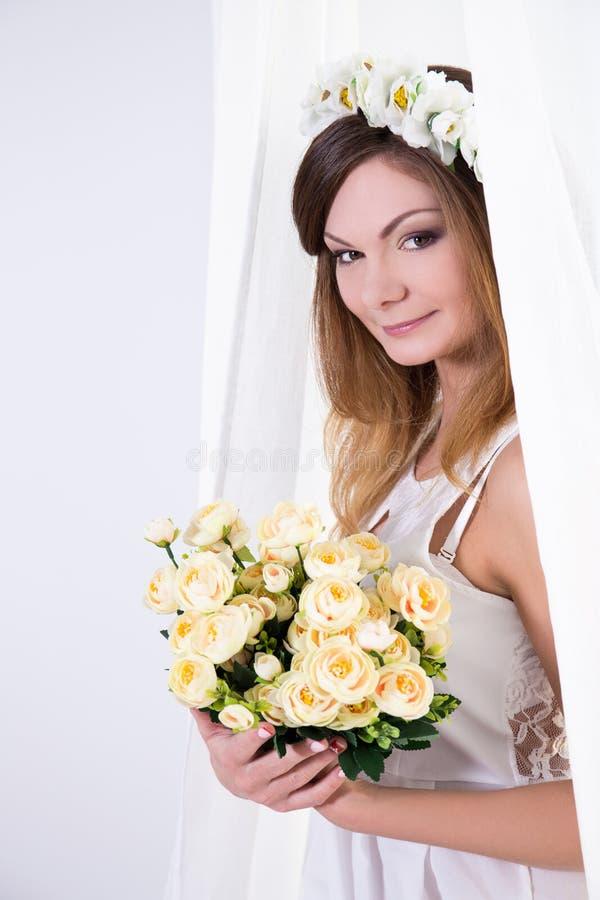 Mooie bruid in witte kleding met bloemen die zich dichtbij wi bevinden stock foto