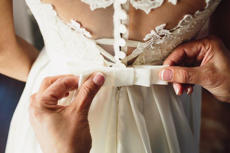 Mooie bruidkleding Getuige die een kleding van het booghuwelijk op de bruid binden stock afbeelding