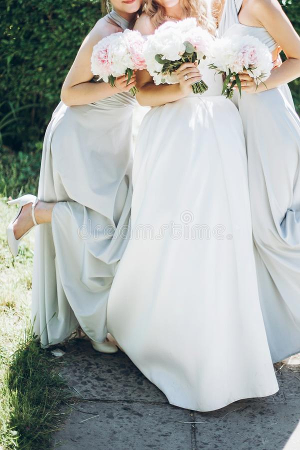 Mooie bruidsmeisjes en bruid die modieuze pioenboeketten houden royalty-vrije stock afbeeldingen