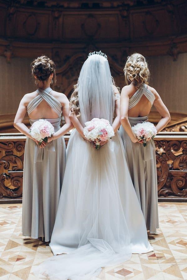 Mooie bruidsmeisjes en bruid die modieuze pioenboeketten o houden royalty-vrije stock foto