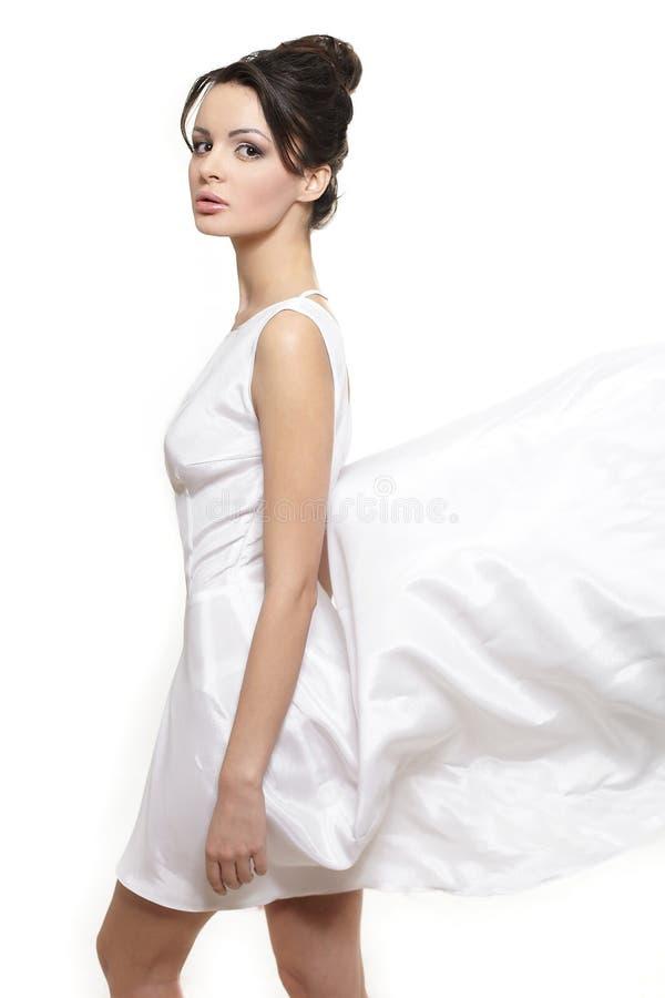 Mooie bruidvrouw die witte vliegende kleding draagt stock foto