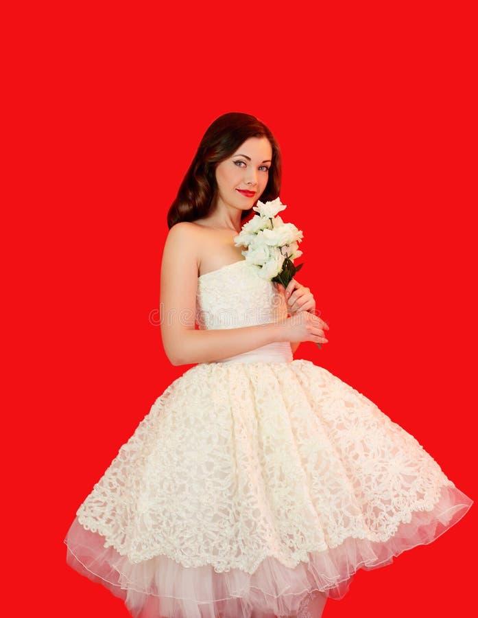 Mooie bruidvrouw in witte huwelijkskleding met boeket van bloemen over kleurrijk rood stock foto's