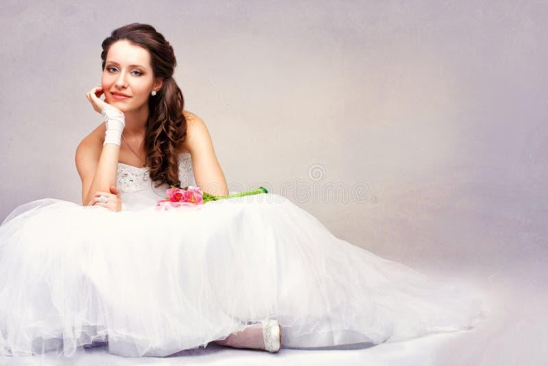 Mooie bruidzitting op de vloer stock foto