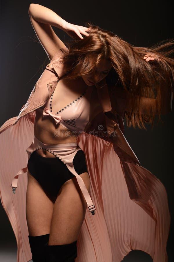 Mooie bruin-haired vrouw in roze ondergoed royalty-vrije stock afbeelding