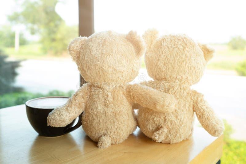 Mooie bruine teddybeer twee zit op houten lijst en koffie latte en kijkt uit het venster van koffiewinkel in de ochtend Liefde, royalty-vrije stock afbeelding