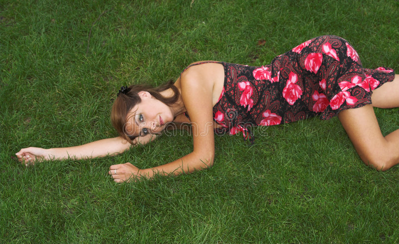 Mooie brunette die op het gras ligt stock foto's