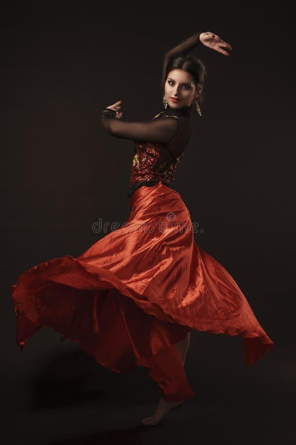 Mooie buikdanser die exotische dans in rode opwindingskleding perfoming royalty-vrije stock fotografie