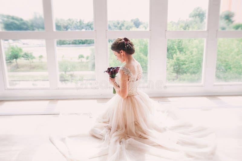 Mooie charmante bruid in een luxueuze kleding die omhoog eruit zien Portret van Gelukkige Bruidzitting in huwelijkskleding in een royalty-vrije stock afbeeldingen