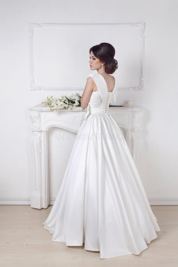 Mooie charmante bruid in huwelijks luxueuze kleding die opnieuw stellen royalty-vrije stock foto