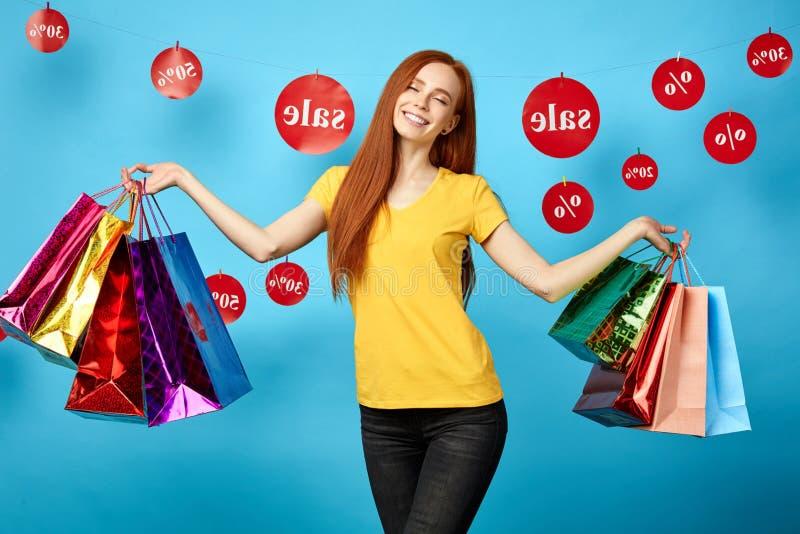 Mooie charmante vrouw die met gesloten ogen het winkelen zakken houden stock afbeelding