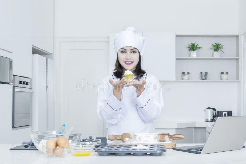 Mooie chef-kok die cupcake tonen royalty-vrije stock foto