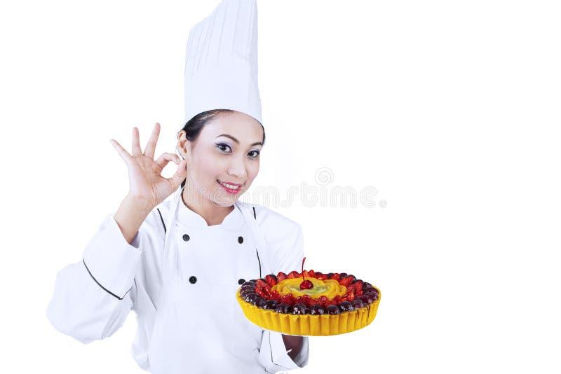 De mooie chef-kok dient heerlijke cake royalty-vrije stock fotografie
