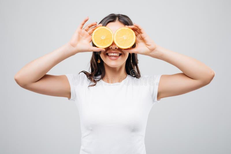Mooie close-up jonge die vrouw met sinaasappelen op witte achtergrond wordt geïsoleerd Gezond voedselconcept Huidzorg en schoonhe stock afbeelding